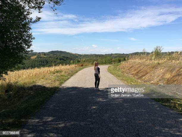 Side View Of Woman Standing On Road Against Sky