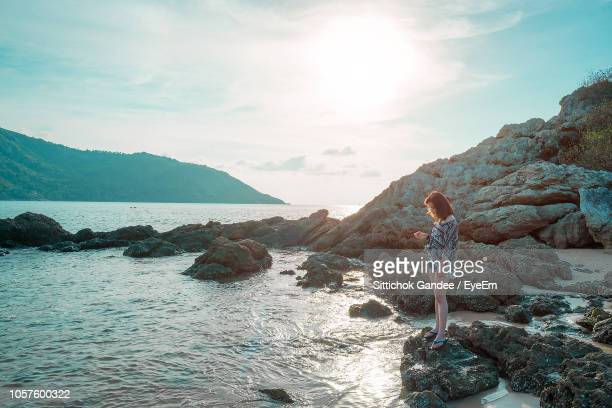 Side View Of Woman Standing On Rocky Shore Against Sky