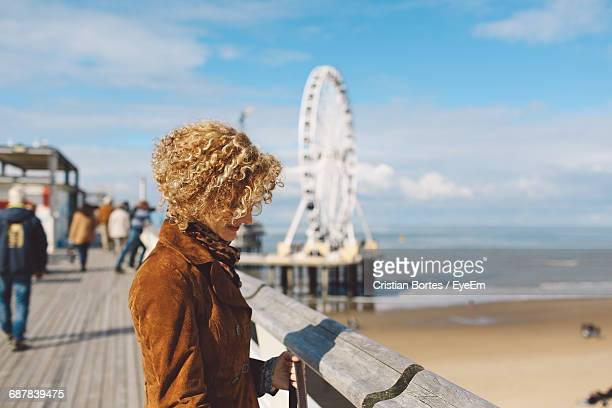 side view of woman standing on scheveningen pier at beach during sunny day - bortes stock pictures, royalty-free photos & images