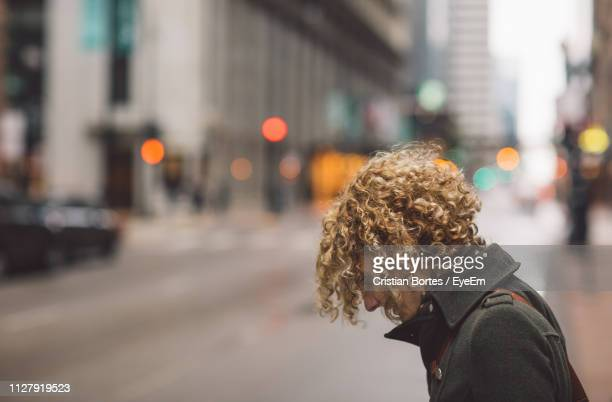 Side View Of Woman Standing On Sidewalk In City
