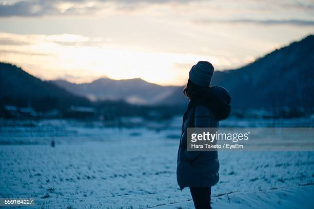 Side View Of Woman Standing On Snowcapped Field