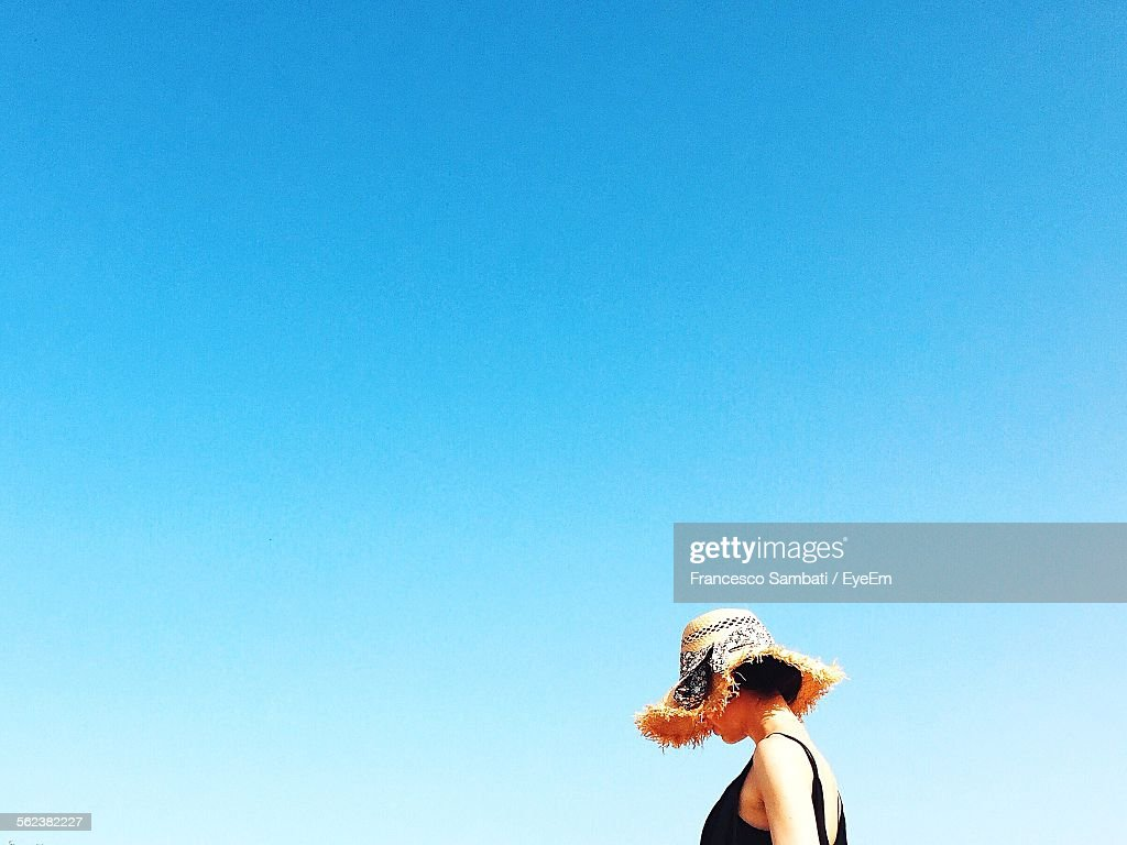 Side View Of Woman Standing Outdoors Against Clear Blue Sky : Stock Photo