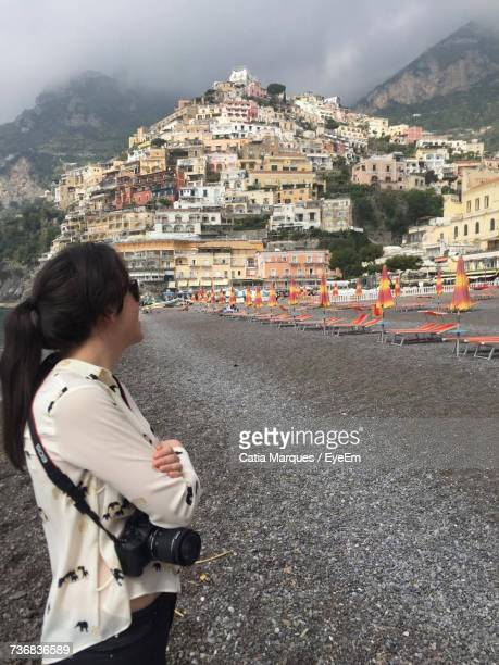 Side View Of Woman Standing With Dslr Camera At Beach In Positano