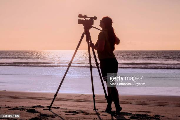 side view of woman standing with movie camera on tripod at beach - photographic film camera stock photos and pictures
