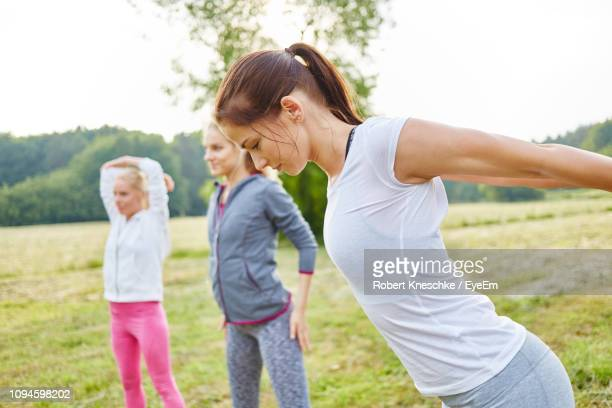 Side View Of Woman Stretching Arms On Field With Friends Standing In Background