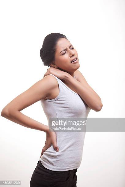 Side view of woman suffering from back and shoulder ache against white background