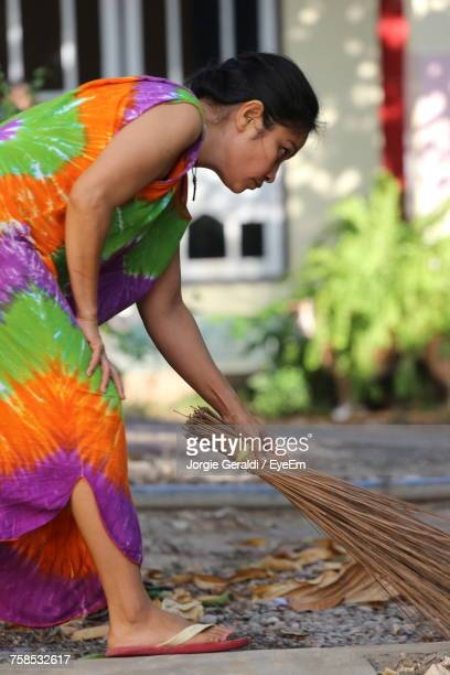 Side View Of Woman Sweeping Footpath With Broom