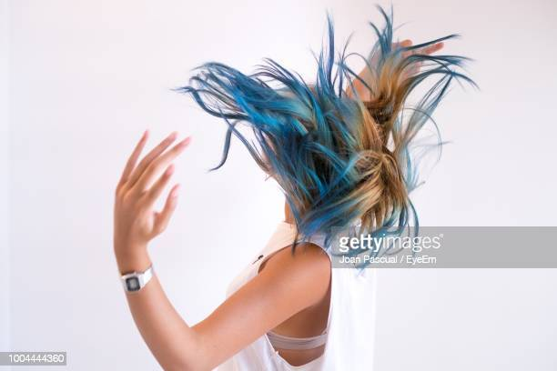side view of woman tossing hair against white background - dyed hair stock pictures, royalty-free photos & images