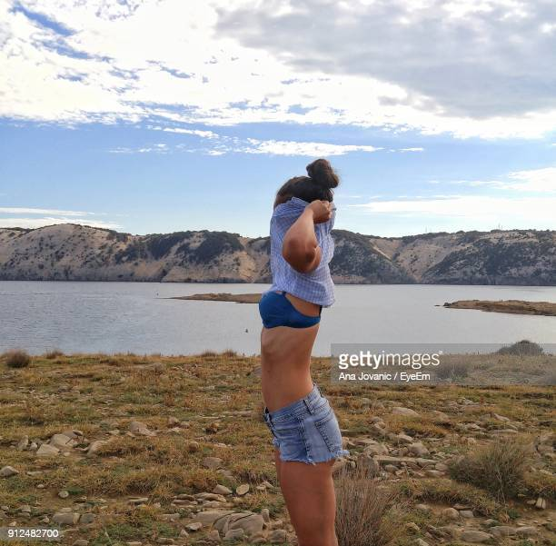 side view of woman undressing while standing against lake - donne mentre si spogliano foto e immagini stock