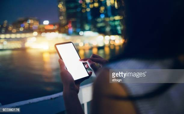 Side view of woman using mobile phone in downtown district at night against illuminated buildings