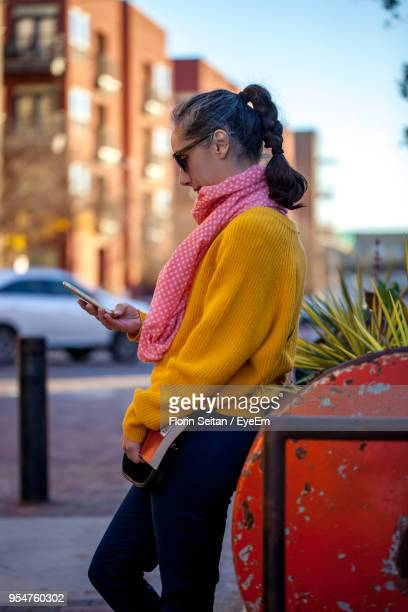 Side View Of Woman Using Mobile Phone On Footpath