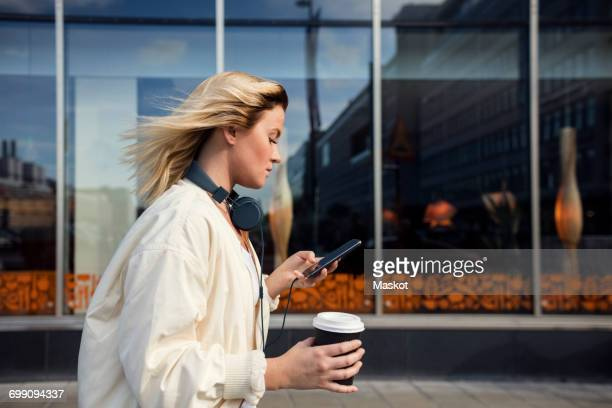 Side view of woman using mobile phone while holding disposable cup against building