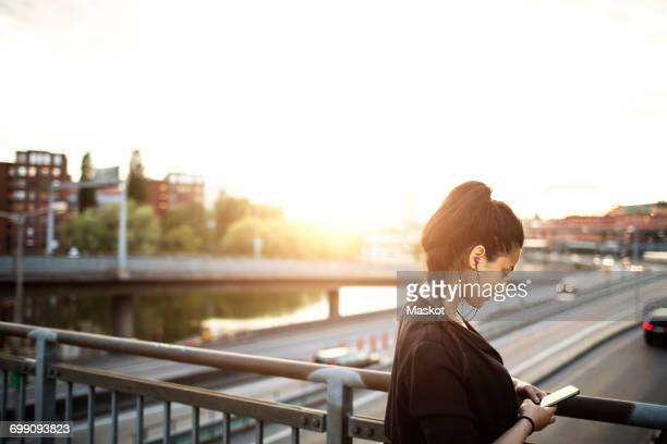 Side view of woman using mobile phone while on standing bridge against sky