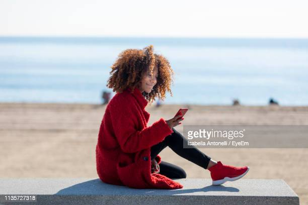 side view of woman using phone while sitting at beach - jeune adulte photos photos et images de collection