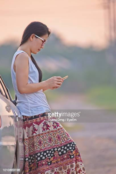 Side View Of Woman Using Phone While Standing By Car During Sunset