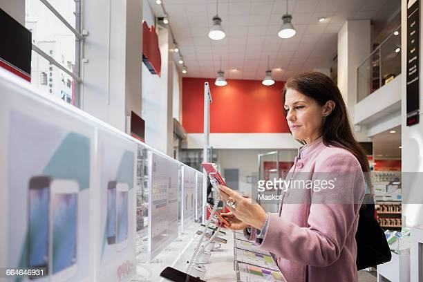 side view of woman using smart phone in store - electronics store stock photos and pictures