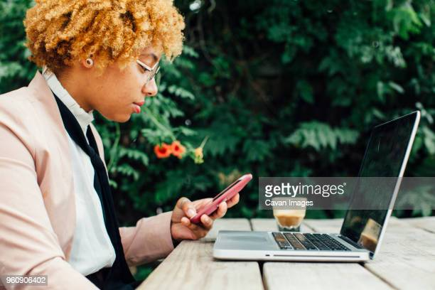 side view of woman using smart phone while sitting at park - cheveux naturels photos et images de collection