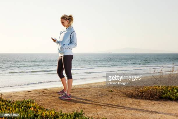 side view of woman using smart phone while standing on shore at beach - mains dans les poches photos et images de collection