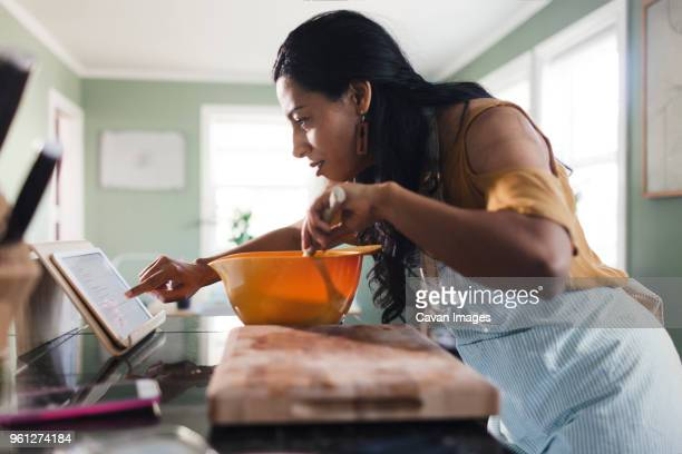 side view of woman using tablet computer for recipe while preparing food in kitchen - recipe stock pictures, royalty-free photos & images