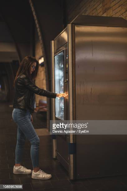 side view of woman using vending machine - vending machine stock photos and pictures
