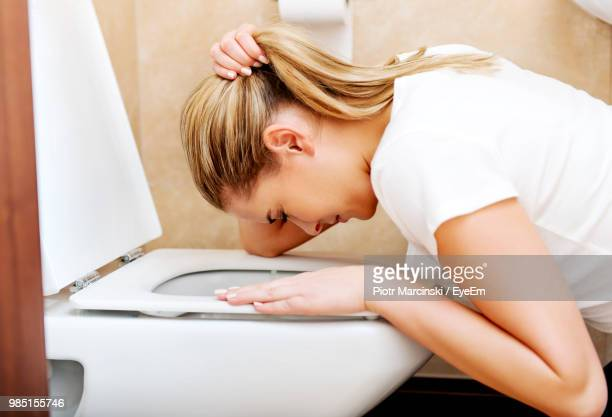 side view of woman vomiting in toilet bowl at bathroom - vomiting stock photos and pictures