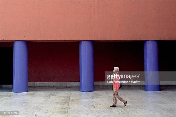 Side View Of Woman Walking Against Blue Columns