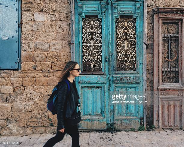 Side View Of Woman Walking Against Old Building