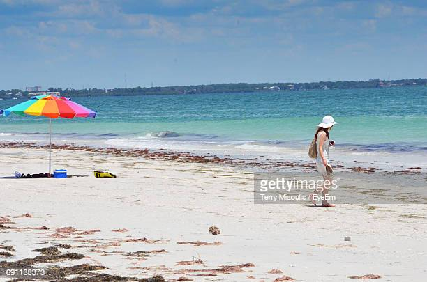 Side View Of Woman Walking At Beach Against Sky