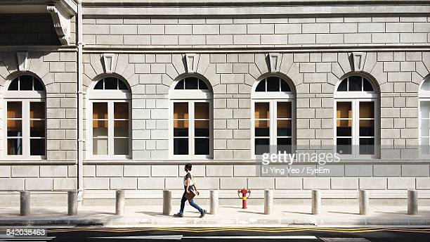 Side View Of Woman Walking On Footpath Against Building