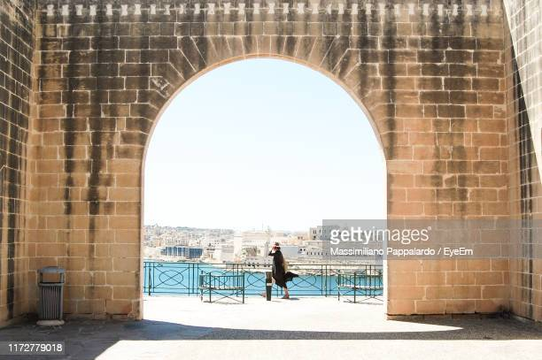 side view of woman walking on footpath in city - malta stock pictures, royalty-free photos & images