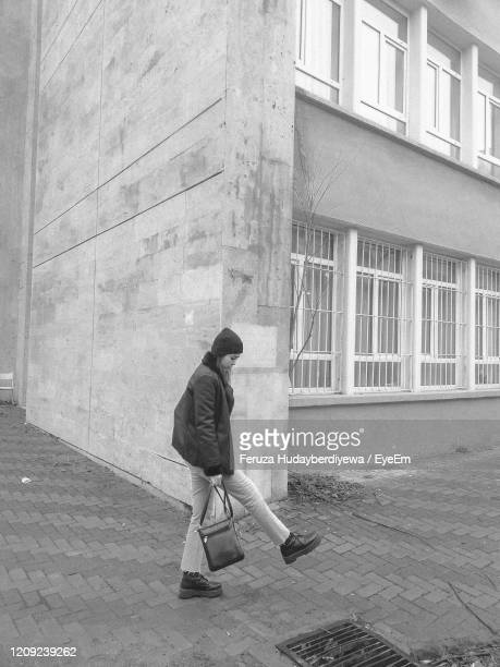 side view of woman walking on sidewalk by building - eskisehir stock pictures, royalty-free photos & images