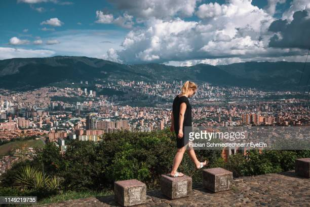 side view of woman walking stone seats with buildings in backgrounds against cloudy sky - medellin colombia stock pictures, royalty-free photos & images