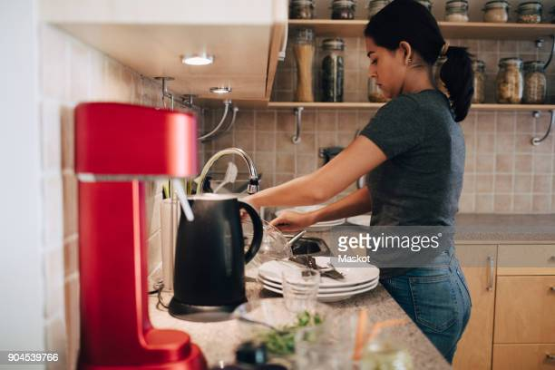 Side view of woman washing utensils in kitchen sink at home
