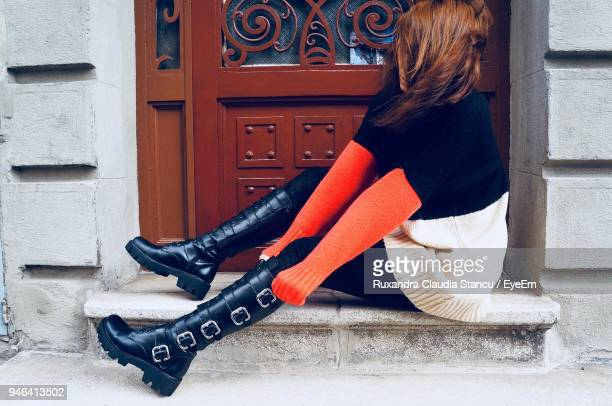 side view of woman wearing black leather boot by door - black boot stock pictures, royalty-free photos & images