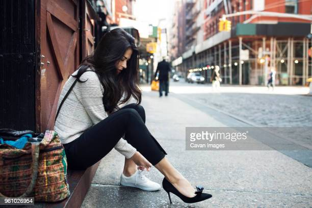 side view of woman wearing canvas shoe on sidewalk - hoge hakken stockfoto's en -beelden