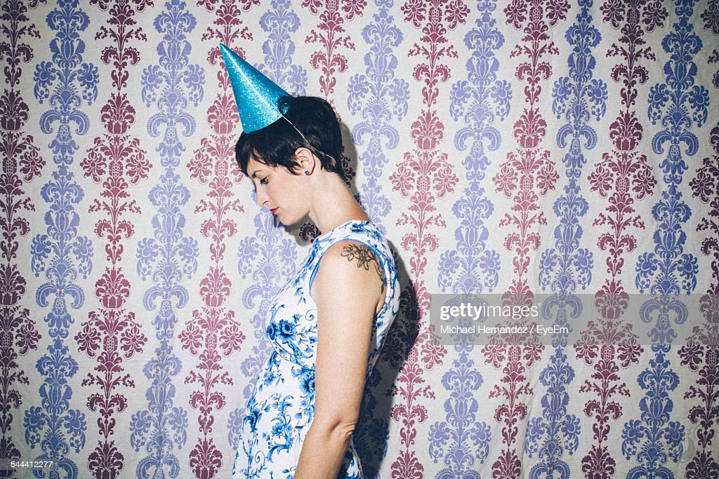 Side View Of Woman Wearing Cap While Standing Against Patterned Wall : Stock Photo
