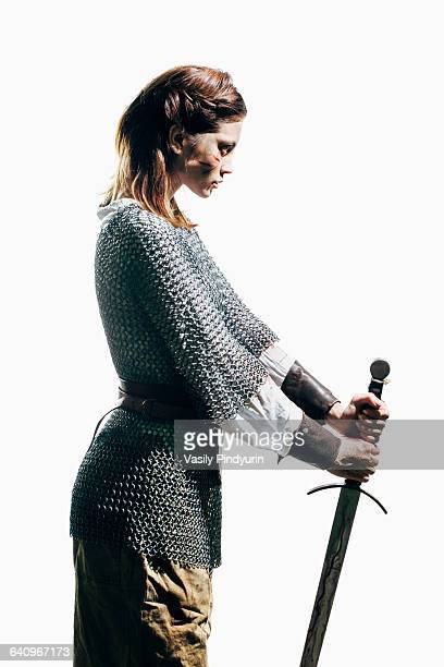 Side view of woman wearing chain mail with sword standing against white background