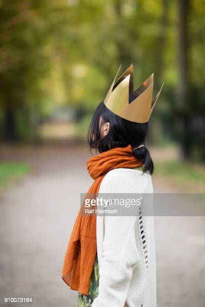 Side view of woman wearing crown while standing at park