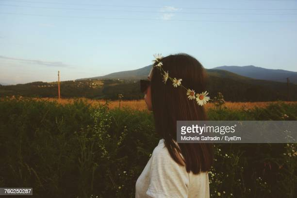 Side View Of Woman Wearing Daisy Flowers Tiara While Standing On Field Against Sky