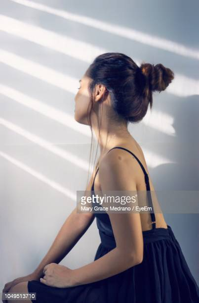 Side View Of Woman Wearing Dress While Sitting Against Wall