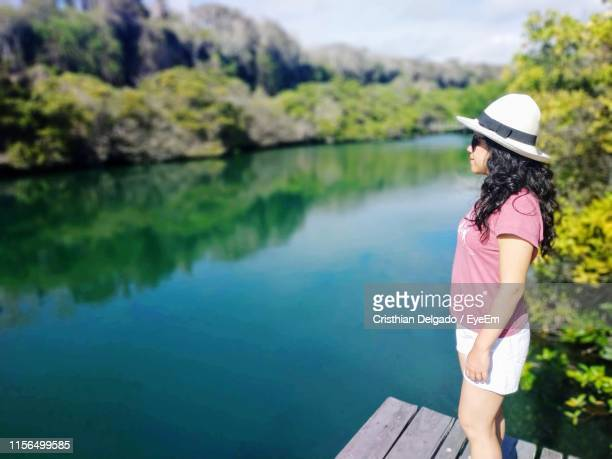 side view of woman wearing hat standing on pier over lake - puerto ayora stock pictures, royalty-free photos & images