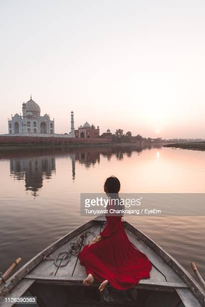 side view of woman wearing red dress sitting on rowboat in lake against sky during sunset - agra stock pictures, royalty-free photos & images