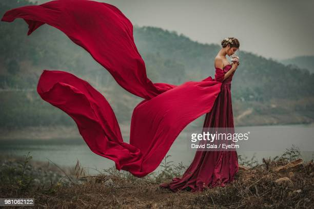 side view of woman wearing red gown by lake - evening gown stock pictures, royalty-free photos & images