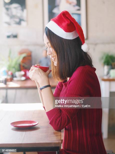 Side View Of Woman Wearing Santa Hat While Drinking Coffee At Home
