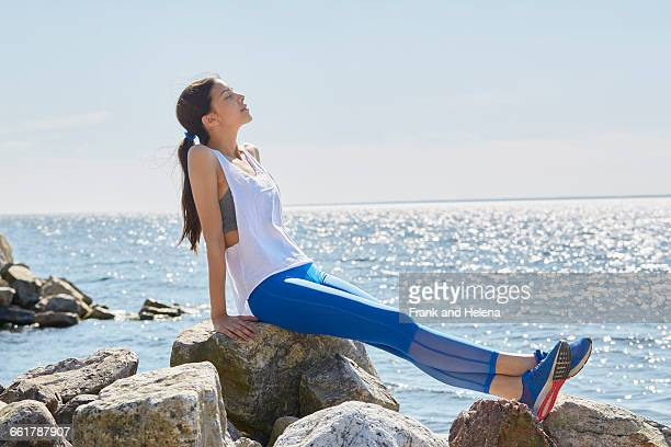Side view of woman wearing sports clothes sitting on rocks basking in sunlight