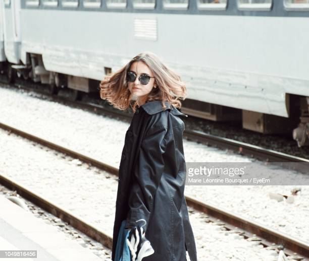side view of woman wearing sunglasses and black overcoat at railroad station platform - marie belle couture foto e immagini stock