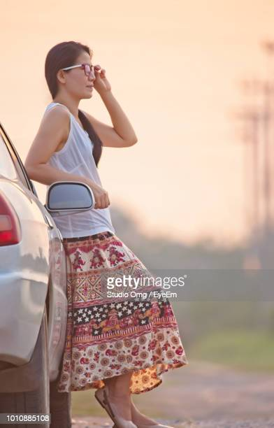Side View Of Woman Wearing Sunglasses Standing By Car During Sunset