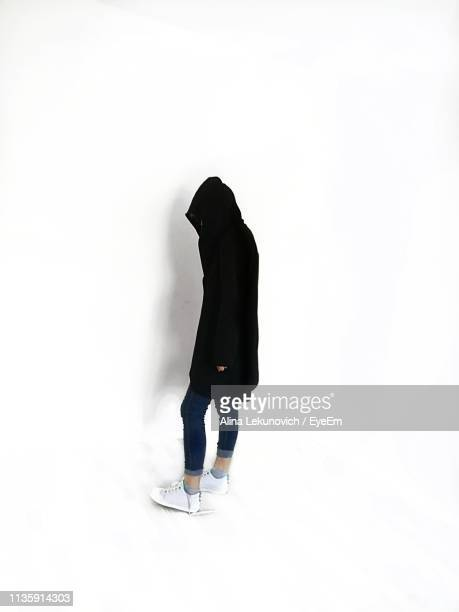 Side View Of Woman Wearing Warm Clothing While Standing Against White Background