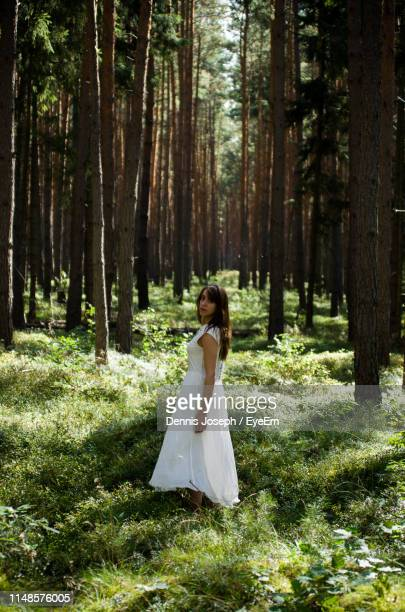 side view of woman wearing white dress while standing on grass in forest - 白のドレス ストックフォトと画像