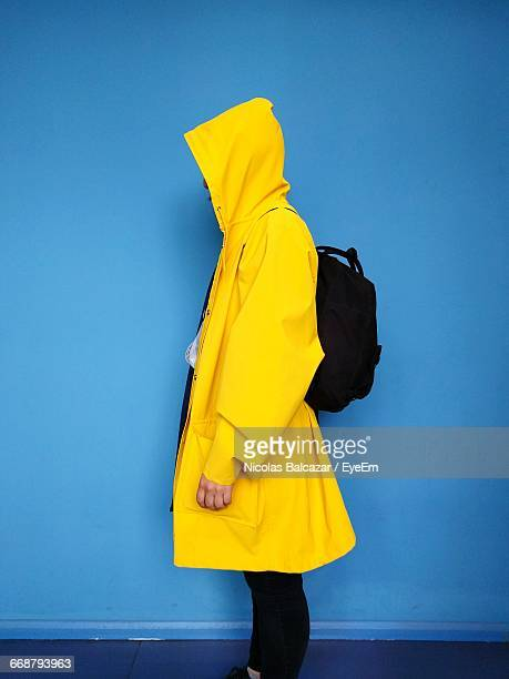 side view of woman wearing yellow raincoat against blue wall - raincoat stock pictures, royalty-free photos & images